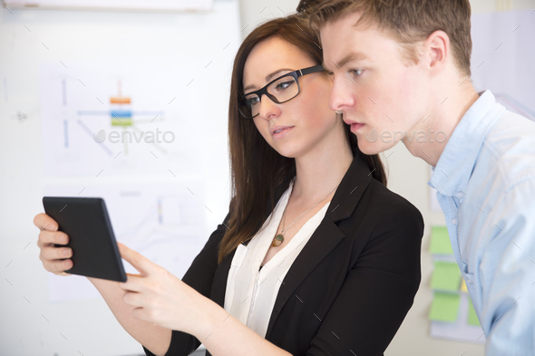 Businesswoman Using Tablet Computer With Male Colleague - Stock Photo - Images