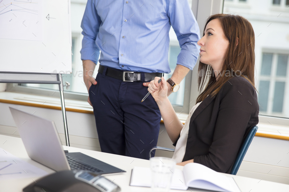 Businesswoman Holding Pen By Colleague In Office - Stock Photo - Images