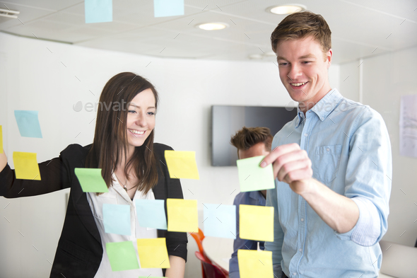 Executives Discussing Over Notes Stuck On Glass In Office - Stock Photo - Images