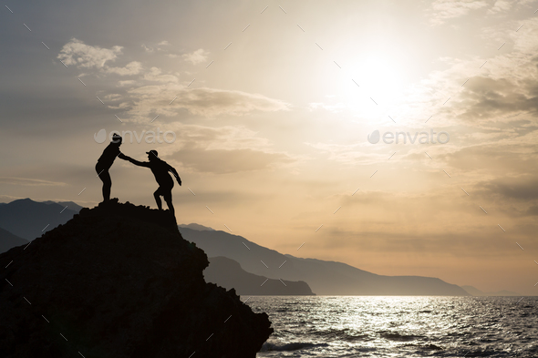 Teamwork couple climbing hiking with helping hand - Stock Photo - Images