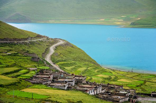 Traditional tibetan homes above Yamdrok Tso Lake lake - Stock Photo - Images