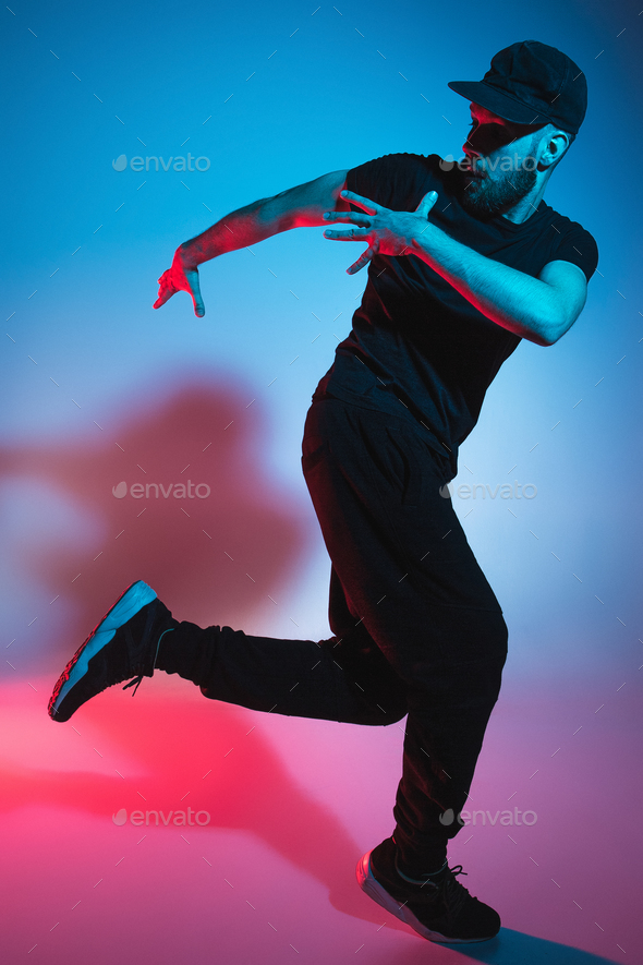 The silhouette of one hip hop male break dancer dancing on colorful background - Stock Photo - Images