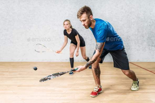 Couple with squash rackets, indoor training club - Stock Photo - Images
