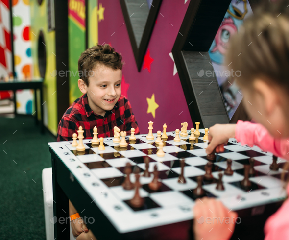 Little kids playing chess in entertainment center - Stock Photo - Images