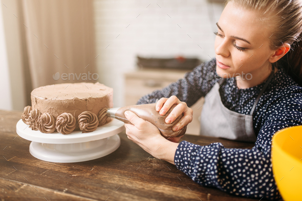Woman decorate cake with culinary syringe - Stock Photo - Images