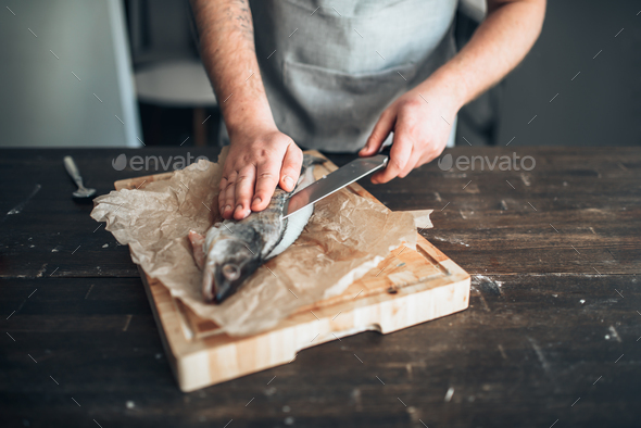 Chef hands with knife cut up fish on cutting board - Stock Photo - Images