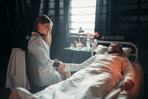 Female doctor measures the pulse of sick man - Stock Photo - Images