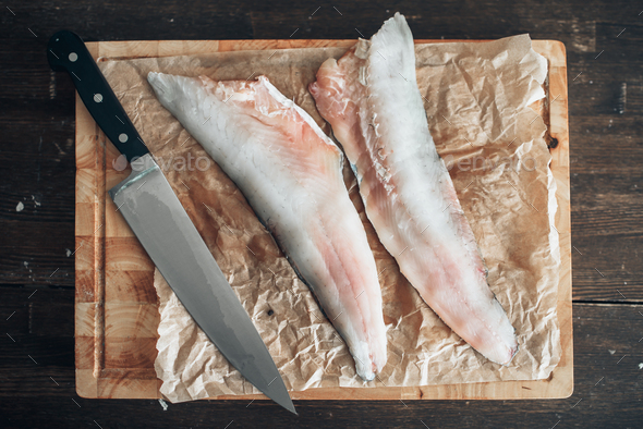 Raw fish slices, knife on cutting board, top view - Stock Photo - Images