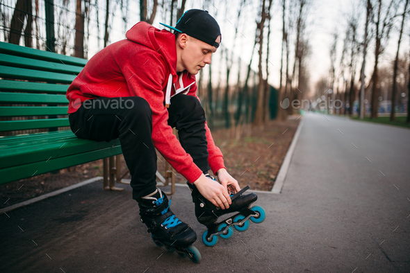 Roller skater sitting on bench and lace up skates - Stock Photo - Images