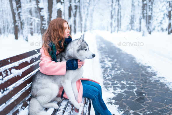 Happy woman sitting on the bench with husky - Stock Photo - Images