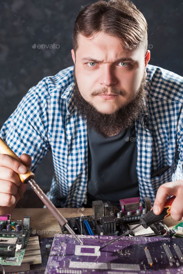 Repairman fixing problem with soldering tool - Stock Photo - Images