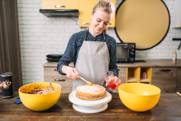 Woman cook hands smears filling for cake - Stock Photo - Images
