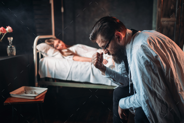 Tired man against sick woman in hospital bed - Stock Photo - Images