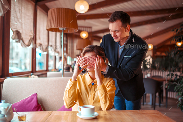 Man closes eyes hands to beautiful woman - Stock Photo - Images