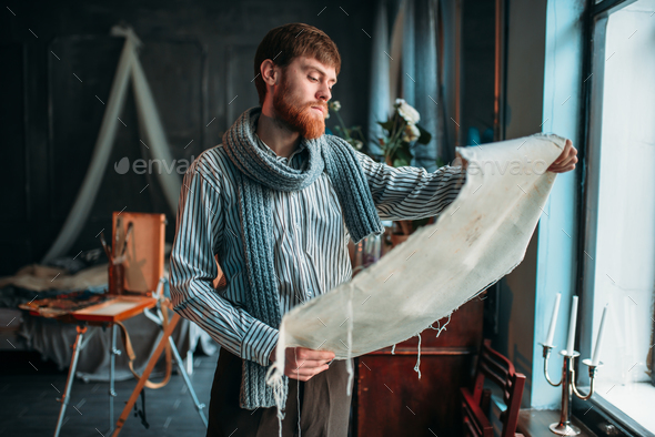 Painter looking at canvas painting against window - Stock Photo - Images
