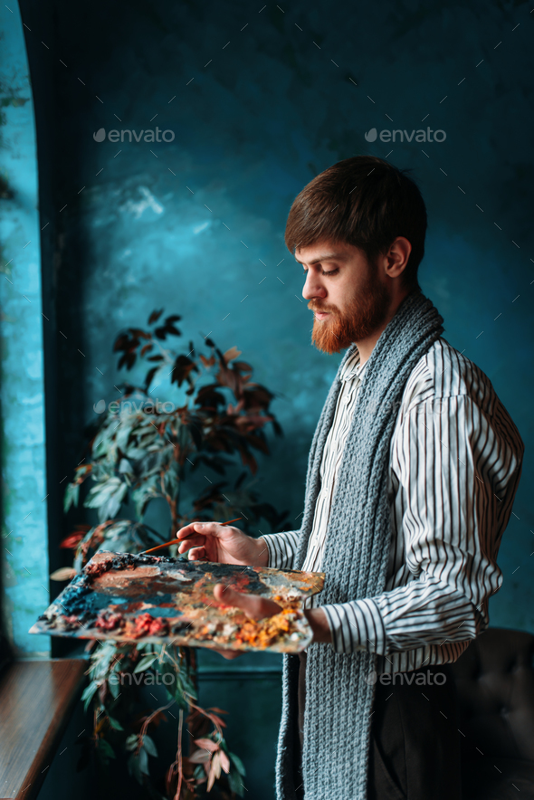 Artist with palette and brush in front of window - Stock Photo - Images