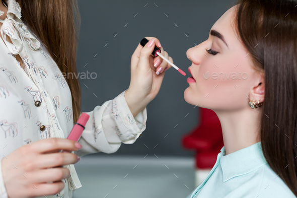 Make up artist applying gloss on woman lips - Stock Photo - Images