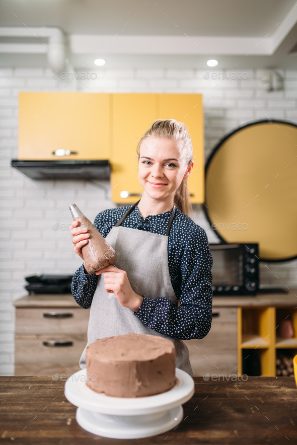 Woman cook in apron holds culinary syringe - Stock Photo - Images