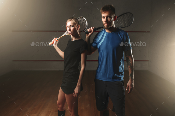 Male and female squash game players with rackets - Stock Photo - Images