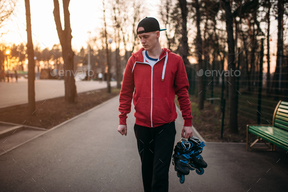 Young man with roller skates in hands - Stock Photo - Images