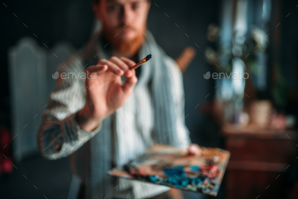 Painter with brush in hand selective focus - Stock Photo - Images