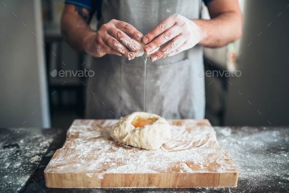 Chef hands mix dough with egg, bread preparation - Stock Photo - Images