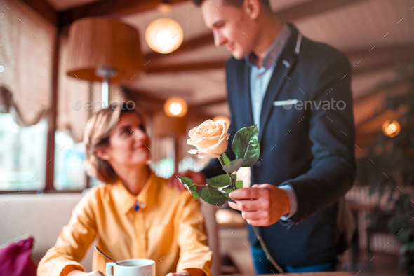 Man in suit gives rose flower to young happy woman - Stock Photo - Images