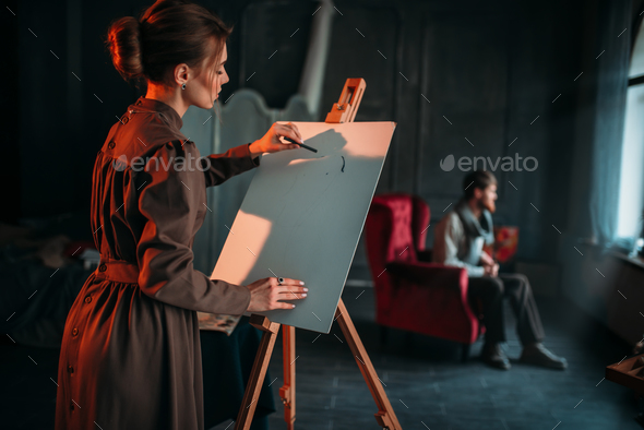 Female painter paints man portrait in art studio - Stock Photo - Images