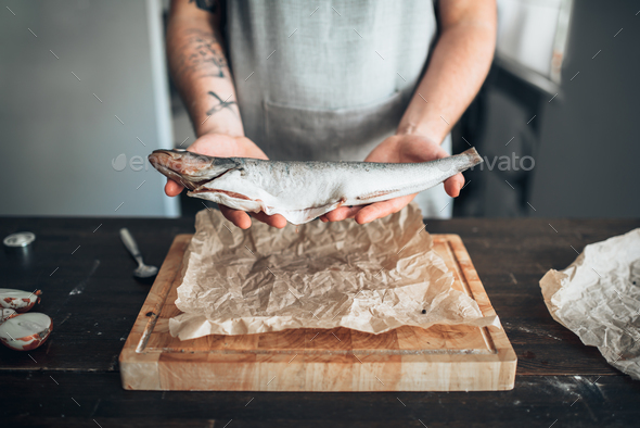 Chef hands holds raw fish over cutting board - Stock Photo - Images