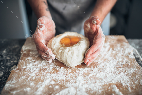 Male baker hands mix the dough with egg - Stock Photo - Images