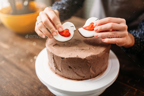 Female hands decorate cake with cookies - Stock Photo - Images