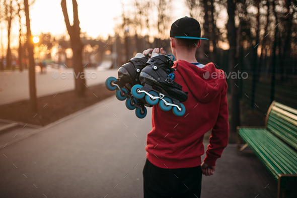 Roller skater with skates in hands, back view - Stock Photo - Images