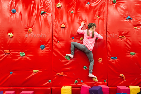 Girl climbing on a wall in attraction playground - Stock Photo - Images