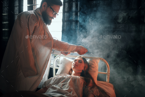 Man standing against ill woman in hospital bed - Stock Photo - Images