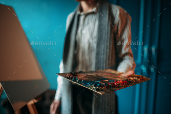 Male painter hand holds palette against the easel - Stock Photo - Images