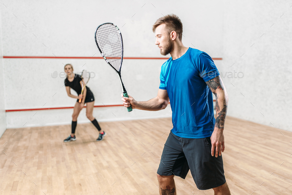 Active couple with rackets play squash game - Stock Photo - Images