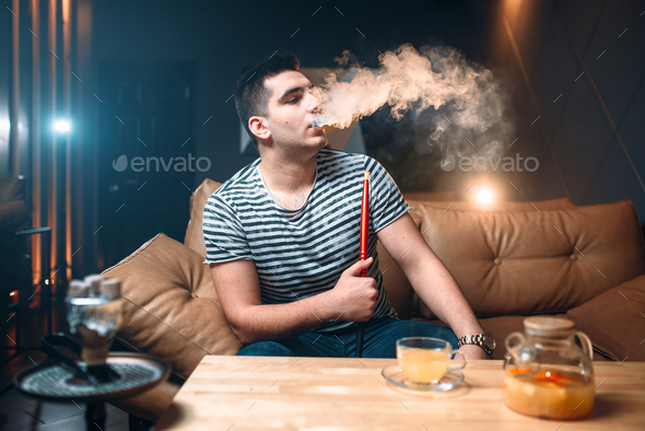 Young man smoking and relaxation at hookah bar - Stock Photo - Images