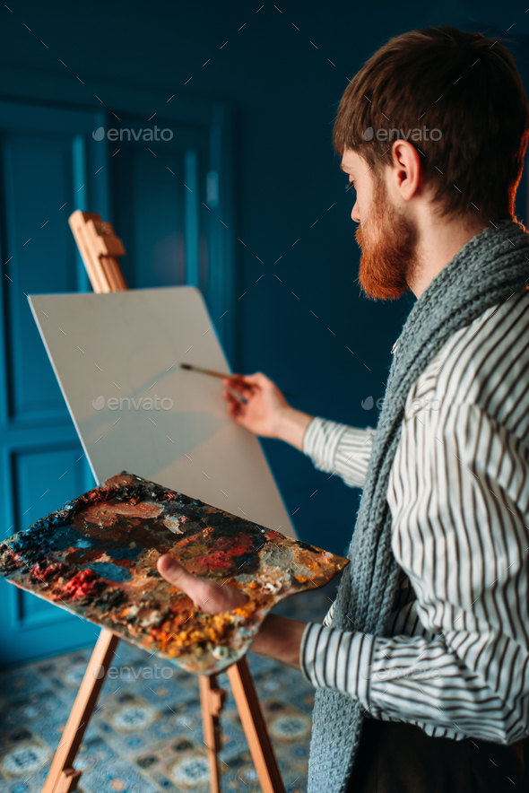Artist with palette and brush in front of easel - Stock Photo - Images