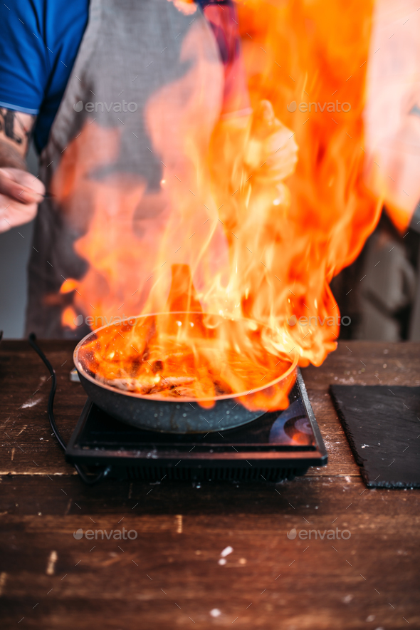 Male person against frying pan with fire - Stock Photo - Images