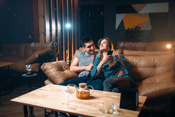 Young couple smoking hookah on leather couch - Stock Photo - Images