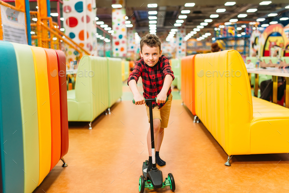 Active boy riding a scooter on playground - Stock Photo - Images