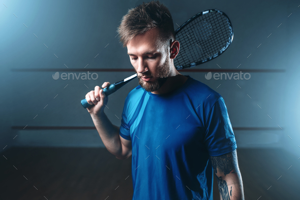 Squash player with racket, indoor training court - Stock Photo - Images
