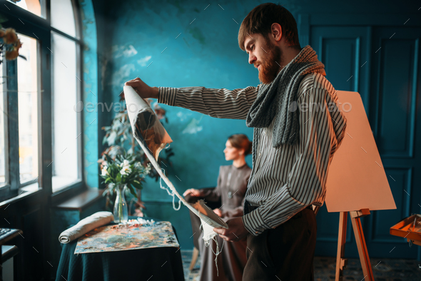 Painter looking at canvas painting against poseur - Stock Photo - Images