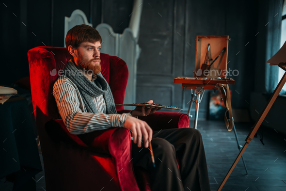 Painter sitting on chair, art studio on background - Stock Photo - Images