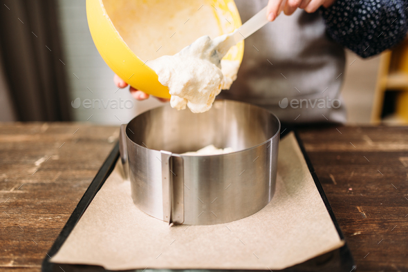Woman cook adds cream for the cake into the pan - Stock Photo - Images