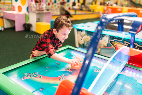 Active boy plays air hockey, entertainment center - Stock Photo - Images