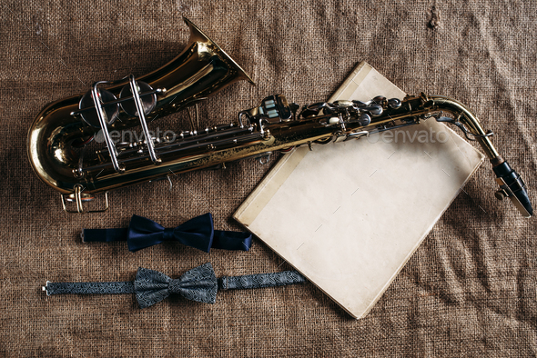 Saxophone, notes and bowtie on canvas background - Stock Photo - Images