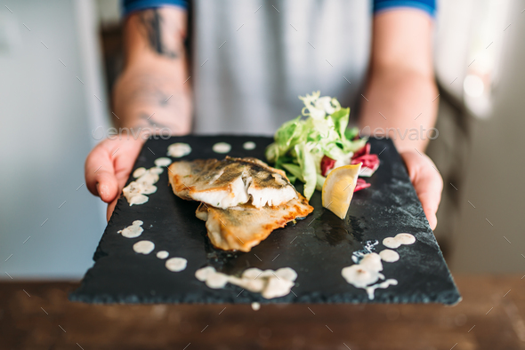 Male hands hold dish of fried fish fillet - Stock Photo - Images