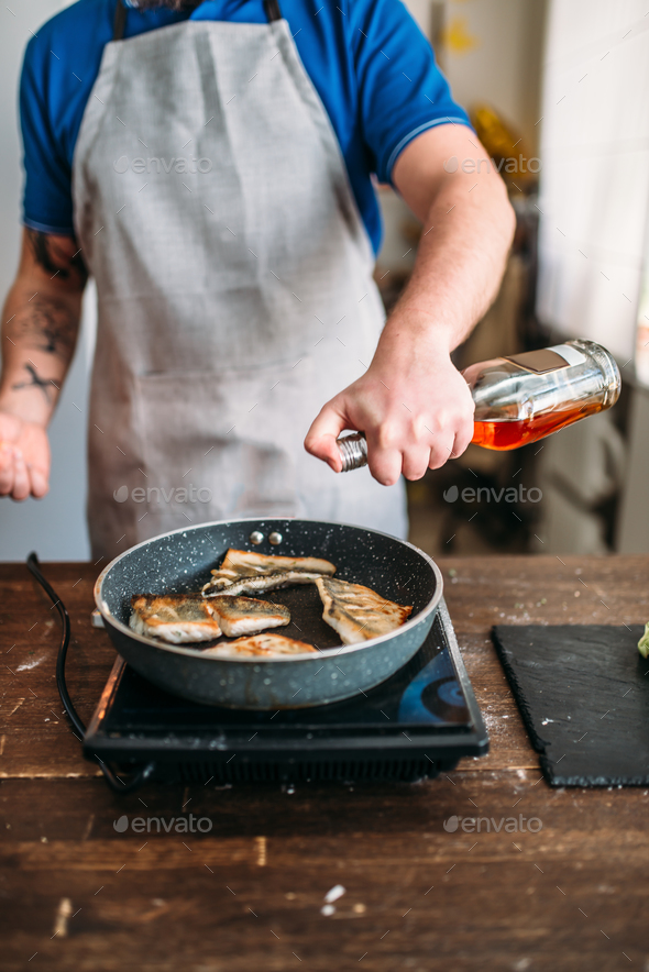 Chef against frying pan with fire, fish cooking - Stock Photo - Images