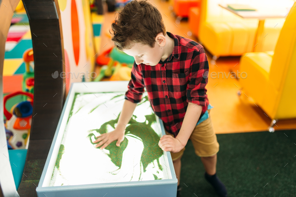 Young boy draws in the sand, entertainment center - Stock Photo - Images